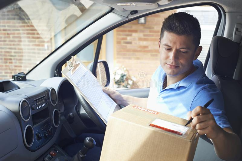 Courier In Van With Clipboard Delivering Package To Domestic House royalty free stock images