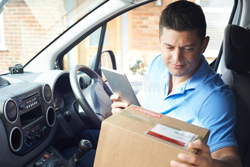 Male Courier In Van With Digital Tablet Delivering Package To House royalty free stock image
