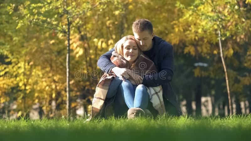 Male covering frozen wife in plaid and hugging her, tender relationship, care stock photos