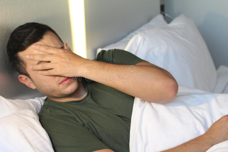 Male covering his face with a hand stock image