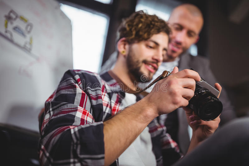 Male coworkers looking in camera at creative office royalty free stock image
