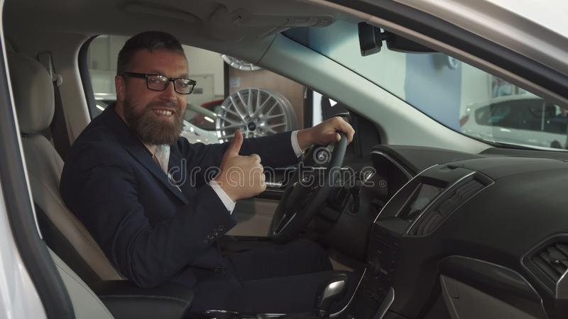 Male customer approves car interior at the dealership royalty free stock photos