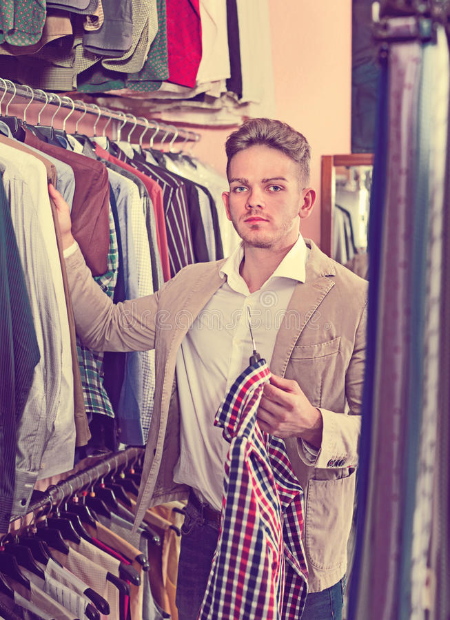Download Male Customer Examining Shirts In Men's Cloths Store Stock Photo - Image: 83701430