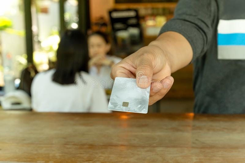 Male customer paying through credit card at coffee shop. Male customer paying through credit card at coffee shop stock photography