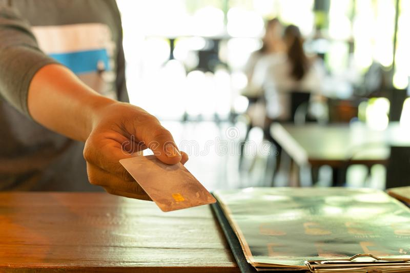 Male customer paying through credit card at coffee shop. Male customer paying through credit card at coffee shop stock photo