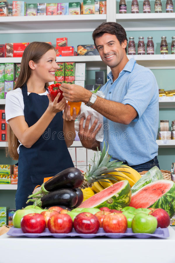 Male Customer With Saleswoman Comparing Bellpepper Stock Images