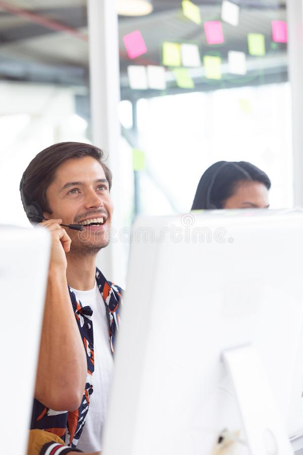 Male customer service executive working on computer at desk. Front view of Caucasian male customer service executive working on computer at desk in office royalty free stock photography