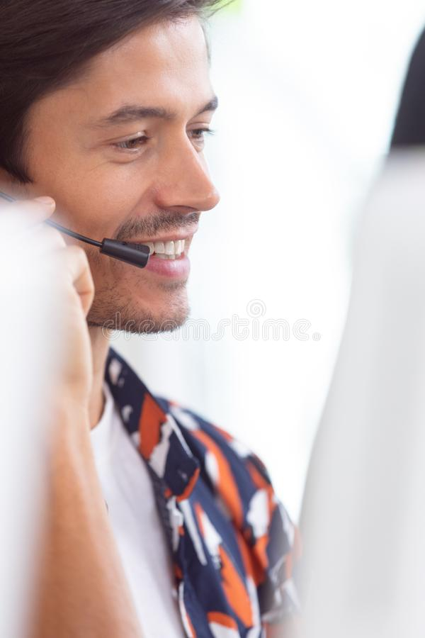 Male customer service executive working on computer at desk. Side view of Caucasian male customer service executive working on computer at desk in office royalty free stock photo