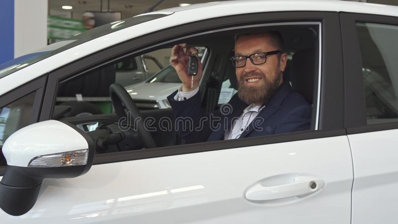 Male customer shows key through the car window stock photo