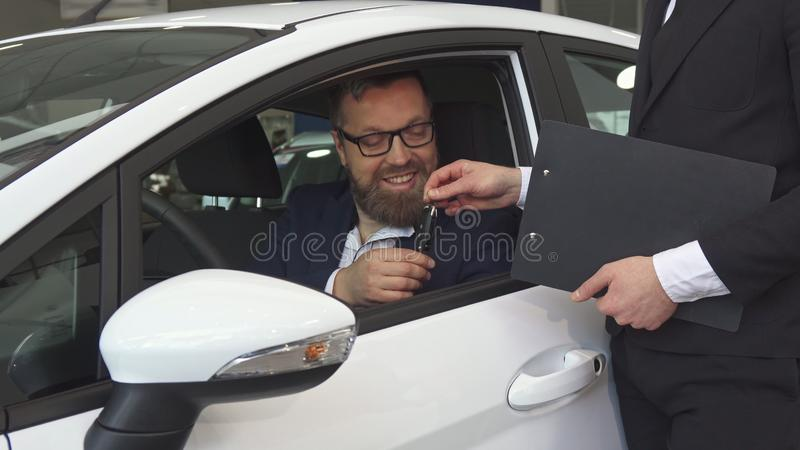 Male customer talks to the sales manager from inside the car stock photo
