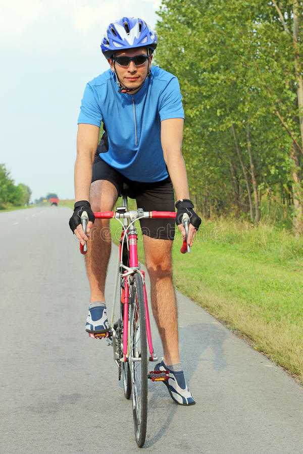 Male cyclist riding a bike on an road stock photography