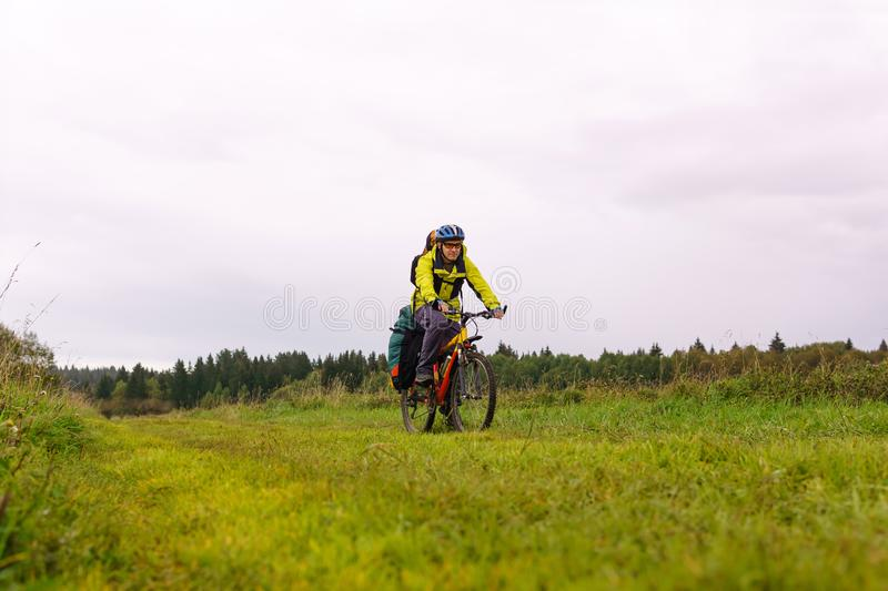 Cyclist traveler rides through an autumn meadow on a cloudy day royalty free stock image