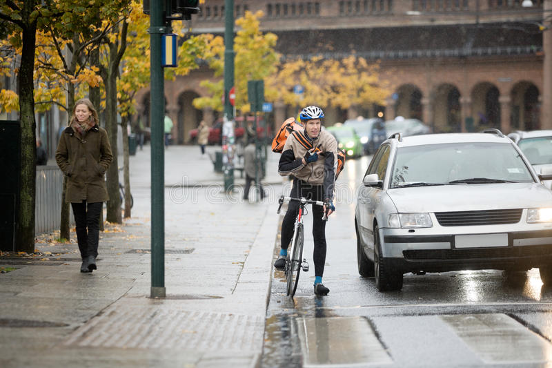 Male Cyclist Using Walkie-Talkie On Street royalty free stock photography