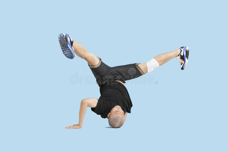 Male dancer doing head stand with legs spread apart over blue background royalty free stock images