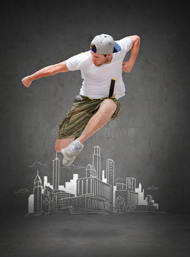 Male dancer jumping in the air. Dancing, happiness and people concept - male dancer jumping in the air with city drawing in the back stock image