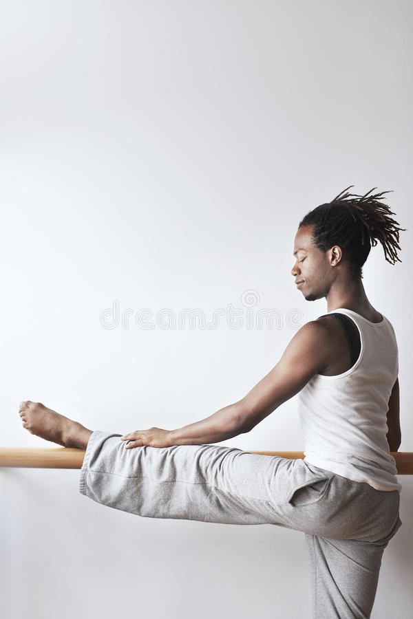 Male Dancer Practicing At Ballet Bar stock photography