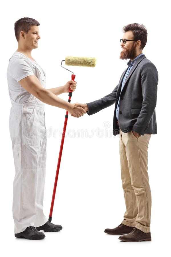 Male decorator with a roller painter shaking hands with a bearded man isolated on white background royalty free stock photography