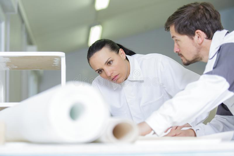 Male decorator and young woman studying repair plan indoors stock image