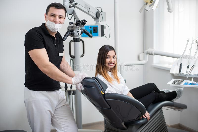 Male dentist with beautiful female patient after treatment in modern dental clinic. Woman sitting in the dental chair stock photography