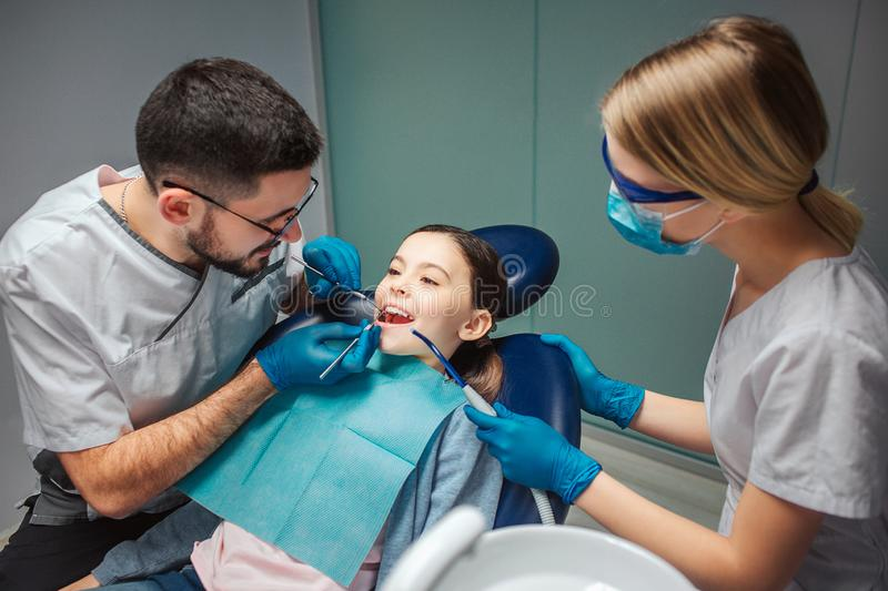 Male dentist check up girl`s teeth with dentist`s tools. Female helper stand beside. Girl sit in dental chair in room royalty free stock images