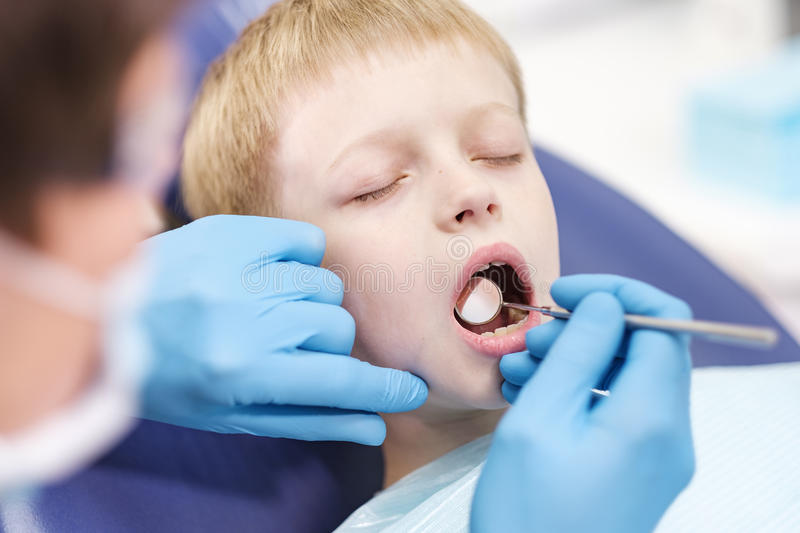 Male dentist examines the teeth of the patient cheerful boy. stock photography