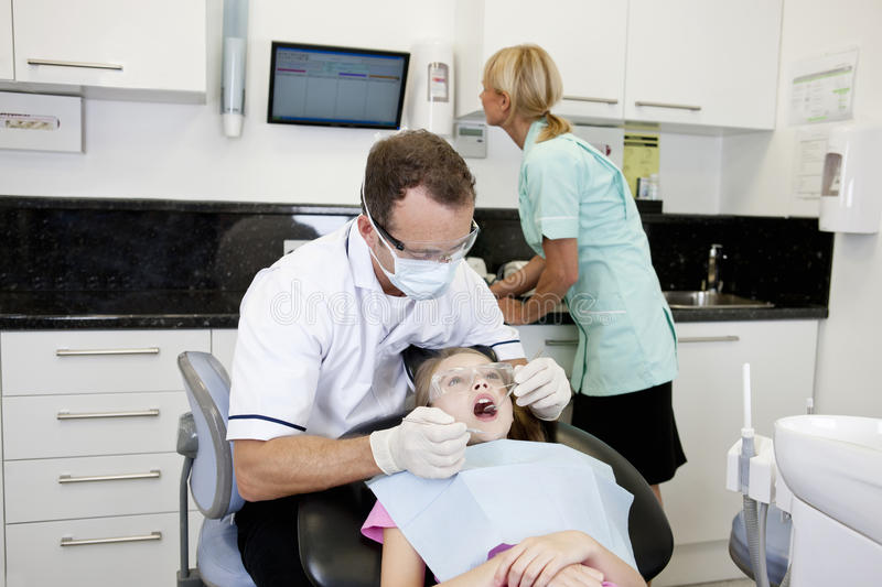 A male dentist examining a young girls teeth, dental nurse in the background royalty free stock image