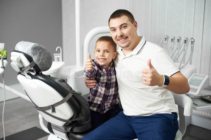 Male dentist and his child client sitting together in a dental office, both being satisfied after the dental treatment stock photography