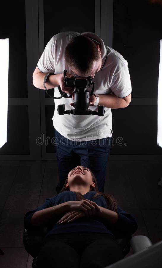 A male dentist is making a picture of his female client`s smile lying on a coach and smiling to him royalty free stock photos
