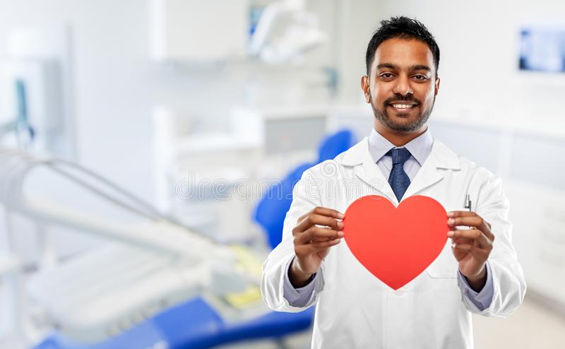 Male dentist with red heart at dental clinic royalty free stock photography
