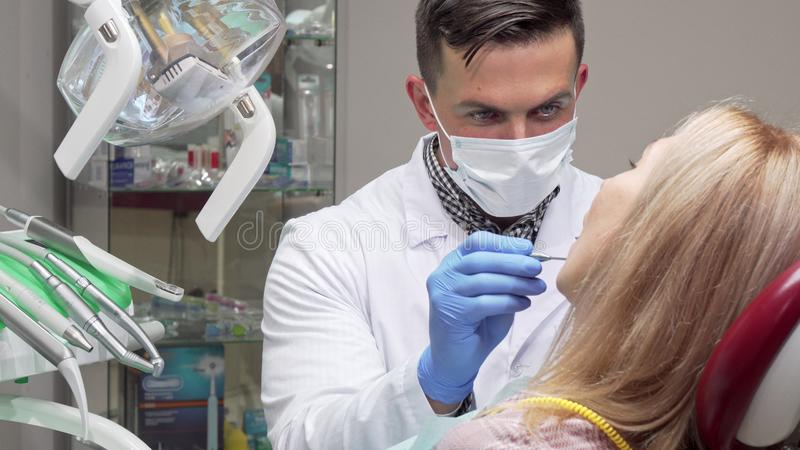 Male dentist wearing medical mask examining teeth of female patient royalty free stock image