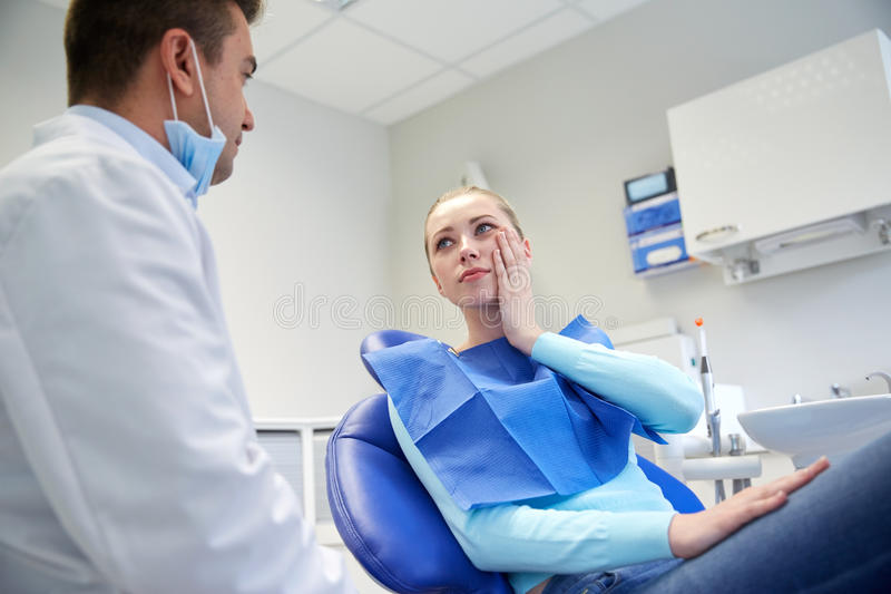 Male dentist with woman patient at clinic. People, medicine, stomatology and health care concept - women patient talking to male dentist and complain of royalty free stock image