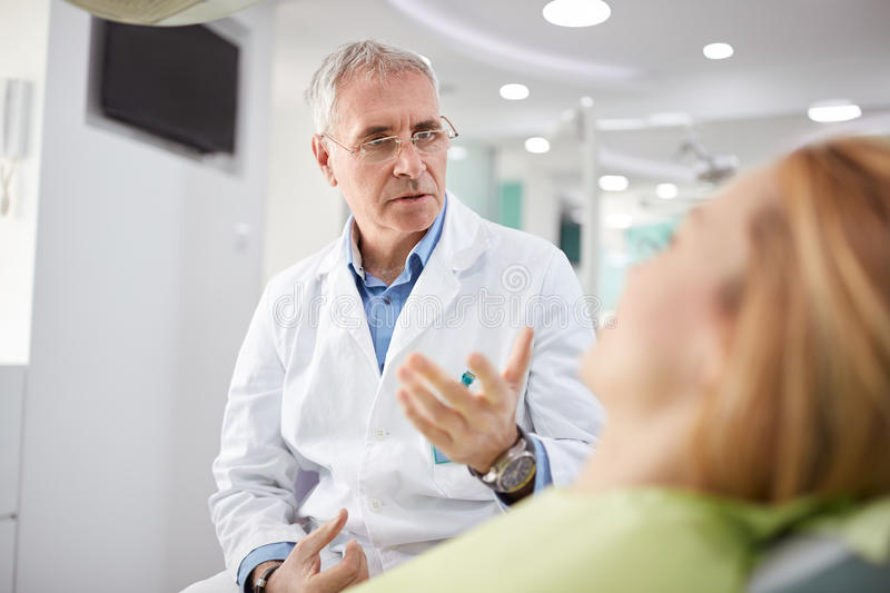 Male dentist on working place in dental practice. Male dentist on working place with female patient in dental practice stock photos