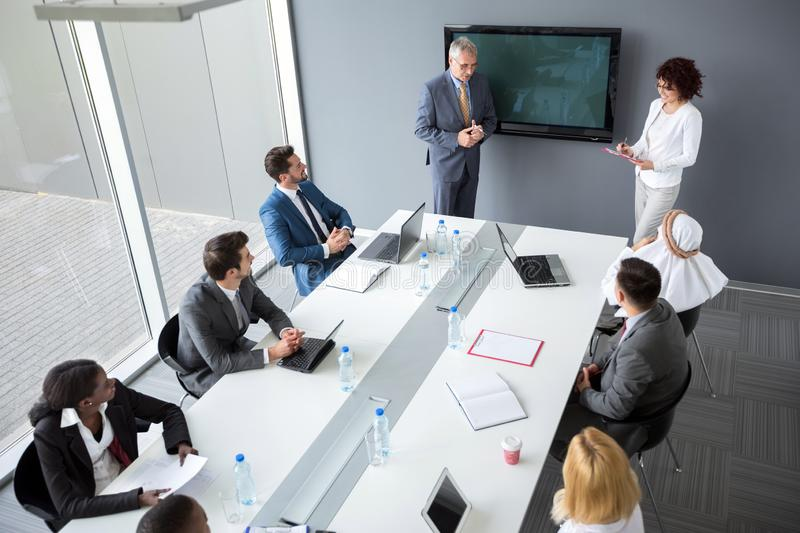 Director and female assistant hold business meeting in company. Male director and female assistant hold business meeting in meeting room royalty free stock image