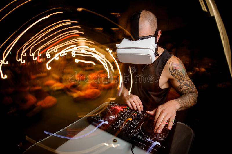 Male DJ in glasses of virtual reality in the process of work royalty free stock photos