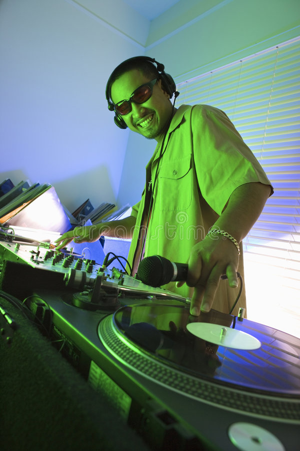 Male DJ with hand on record.