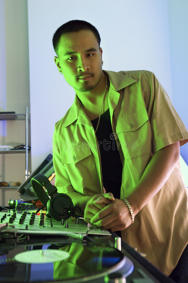 Male DJ leaning on turntable. Asian young adult male DJ leaning on turntable looking at viewer royalty free stock photo