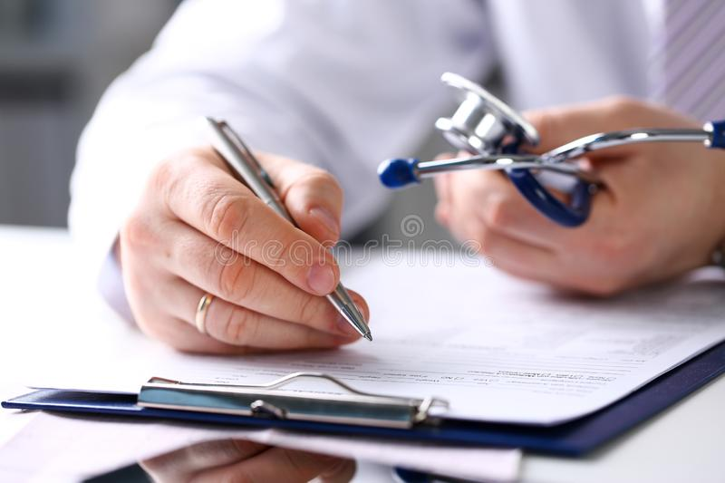 Male doctor arm hold silver pen and pad stock photo
