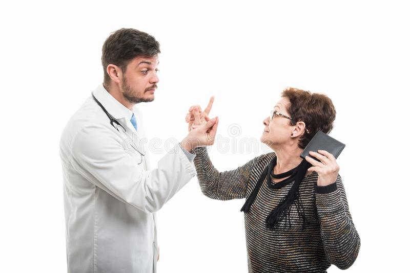 Male doctor asking money to female senior patient stock image