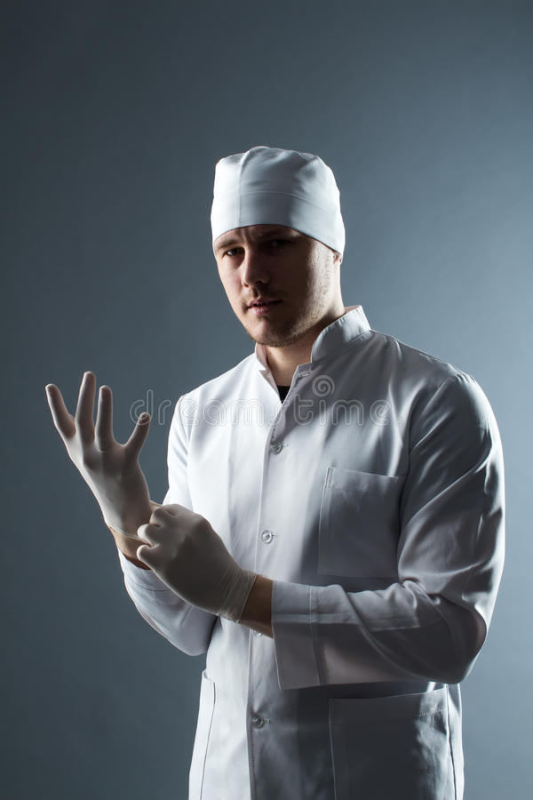 Male doctor in cap with beard wear rubber medical gloves in cont. Rasting light stock image