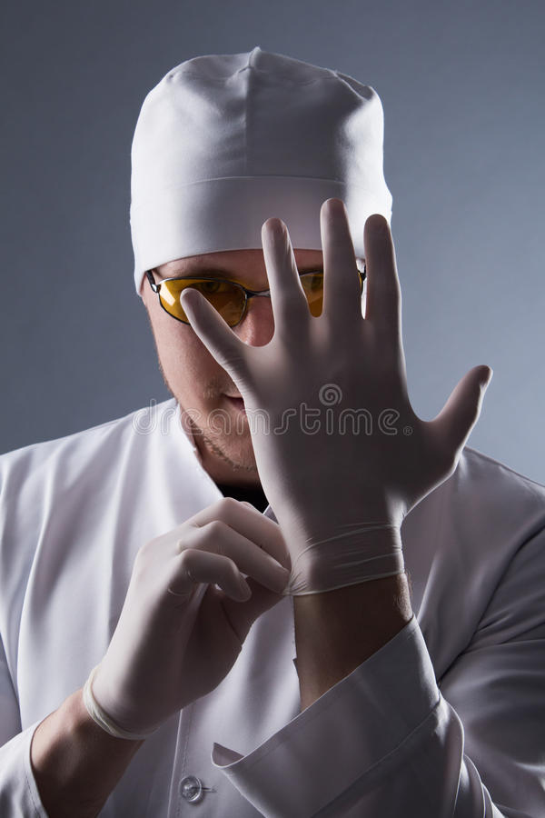 Male doctor in cap and glasses wear rubber medical gloves in con. Trasting light royalty free stock photos