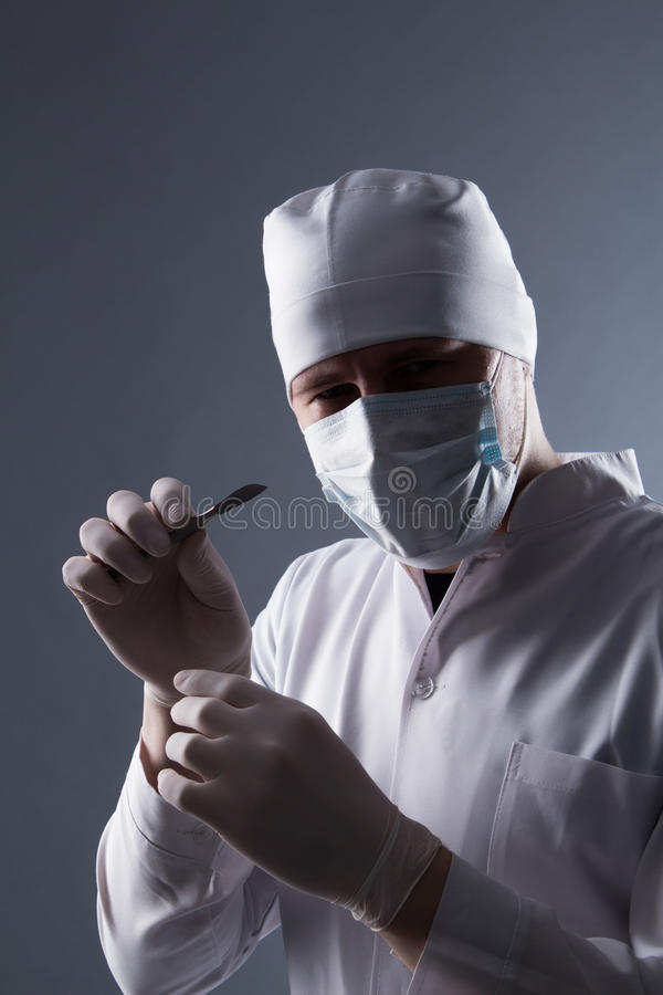 Male doctor in cap, mask and rubber medical gloves holding scalp. El stock photography
