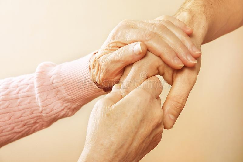 Mature female in elderly care facility gets help from hospital personnel nurse. Close up of aged wrinkled hands of senior woman. G. Male doctor care giver stock images