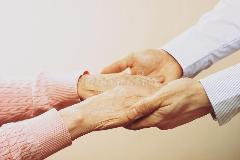 Mature female in elderly care facility gets help from hospital personnel nurse. Close up of aged wrinkled hands of senior woman. G. Male doctor care giver stock photos