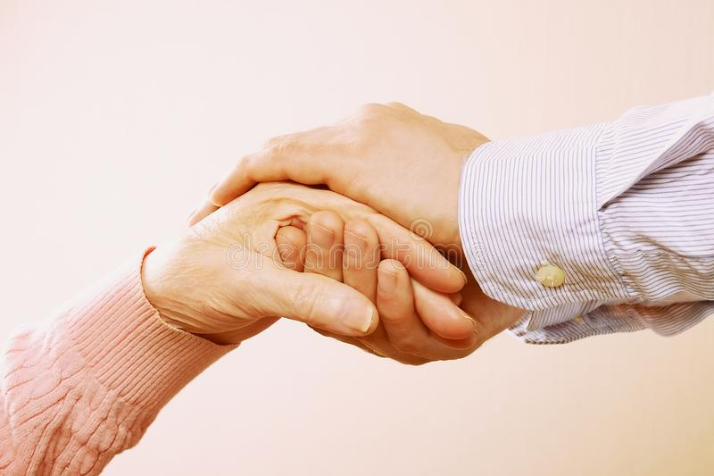 Mature female in elderly care facility gets help from hospital personnel nurse. Close up of aged wrinkled hands of senior woman. G. Male doctor care giver royalty free stock photography