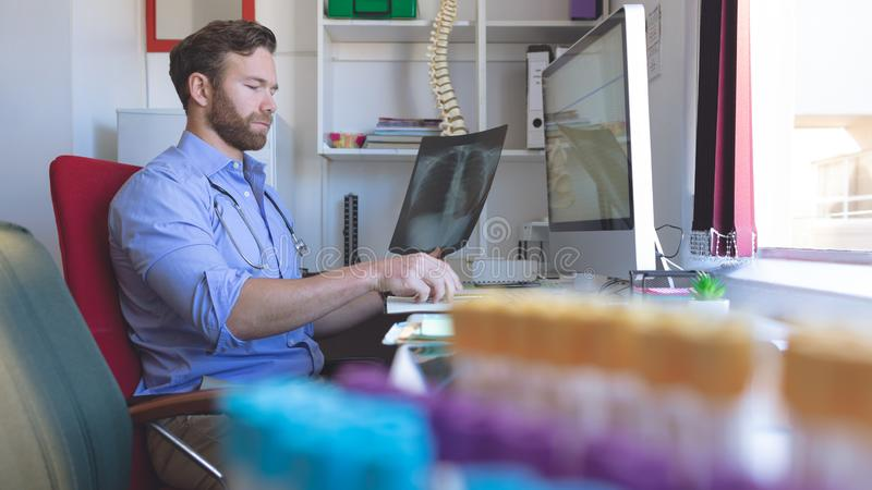 Male doctor checking  x ray report in computer at clinic. Side view of Caucasian male doctor checking  x ray report in computer at clinic royalty free stock image