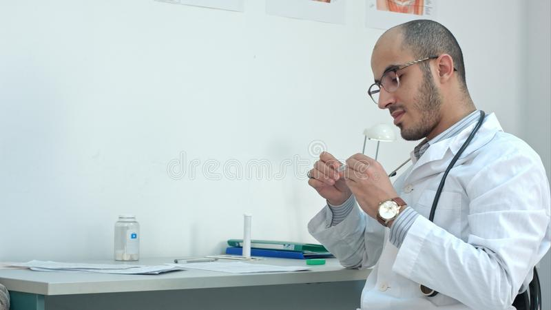 Male doctor checking the temperature on thermometer and filling in medical form royalty free stock photo