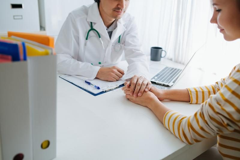 Male doctor cheering up his female patient, holding her hand stock photography