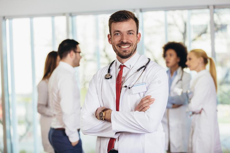 Doctor with colleagues in background, doctor looking at camera with emergency team in background royalty free stock photography