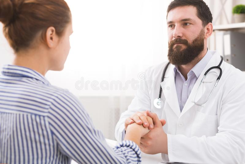 Male doctor comforting patient at consulting room royalty free stock image