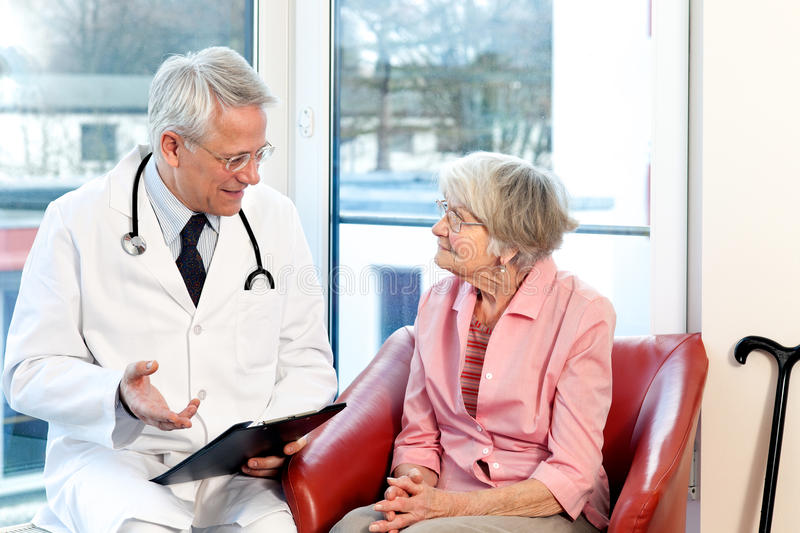 Male doctor in consultation with a senior patient stock photo